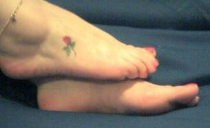 womans sexy foot with painted toe nails and pretty rose tattoo